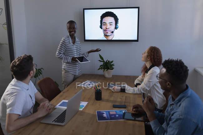 Uomini d'affari che interagiscono tramite videochiamata in conferenza in ufficio — Foto stock