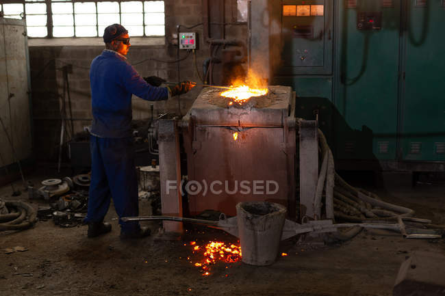 Male worker molting metal in foundry workshop — Stock Photo