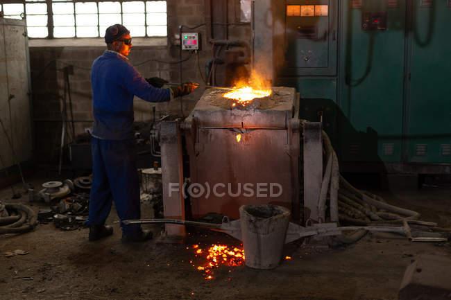 Männliche Arbeiter Häutung Metall in Gießerei-workshop — Stockfoto