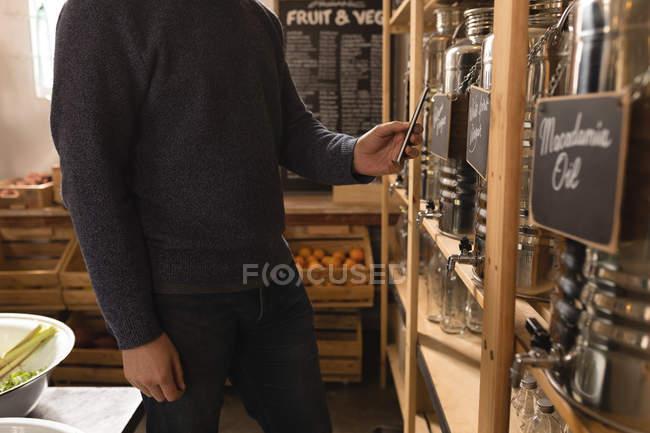 Homem clicando foto do recipiente de vinagre no supermercado — Fotografia de Stock