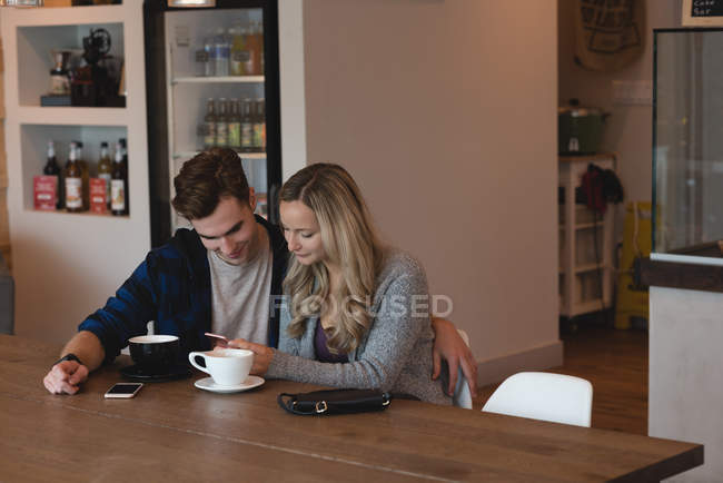 Young couple using mobile phone in cafe — Stock Photo