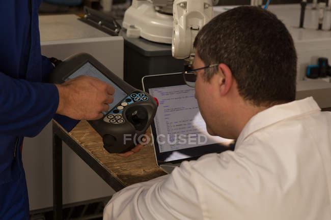 Робототехнические инженеров, обсуждая над пульт дистанционного управления на складе — стоковое фото