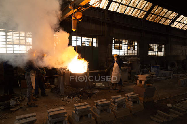 Male workers molting metal in foundry workshop — Stock Photo