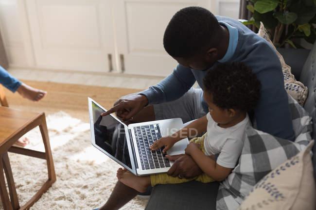 Padre e hijo usando portátil en una sala de estar en casa - foto de stock