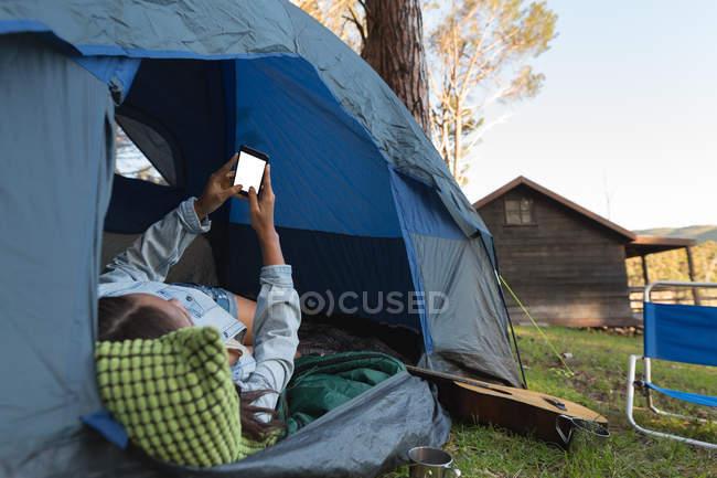 Mulher usando telefone celular na barraca no parque de campismo — Fotografia de Stock