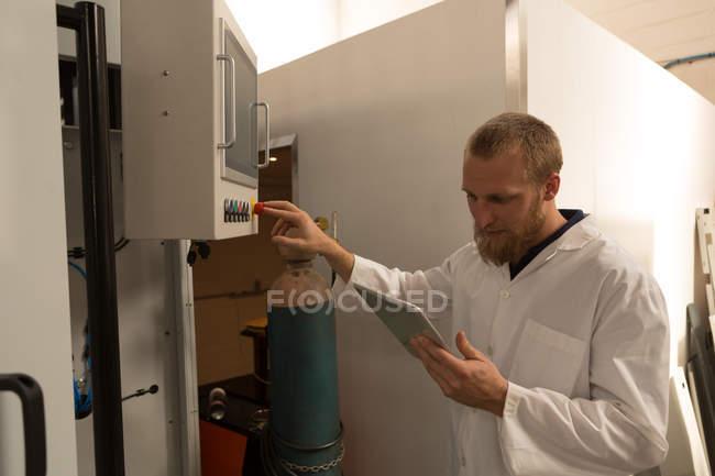 Робототехника инженер, с использованием цифровых таблетки во время контроля панели управления на складе — стоковое фото