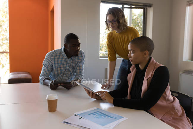 Attentive business executives discussing over digital tablet in office — Stock Photo