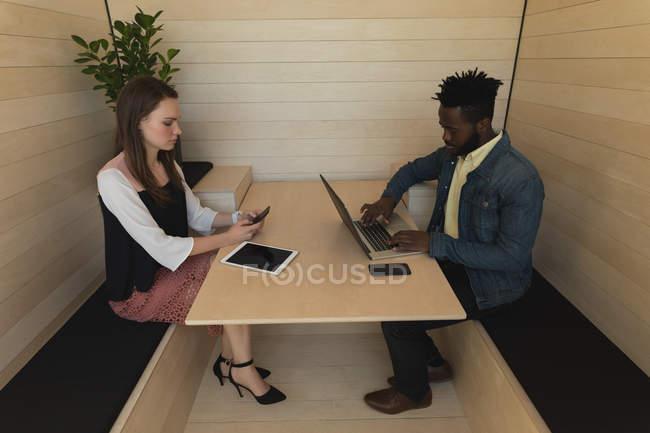 Geschäftskollegen mit Handy und Laptop im Büro — Stockfoto