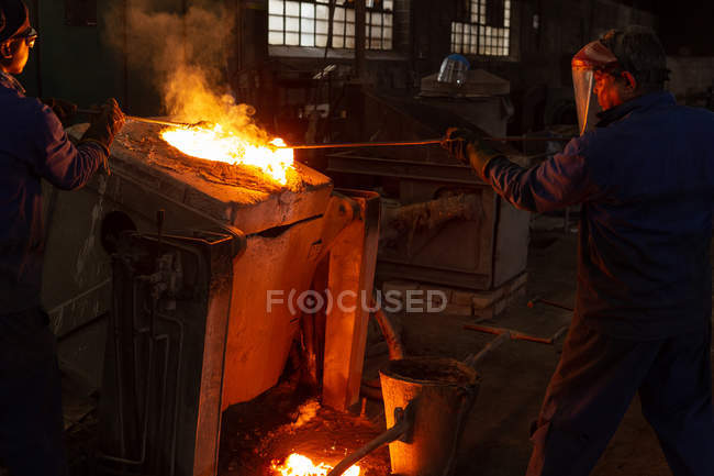 Male workers working in foundry workshop — Stock Photo
