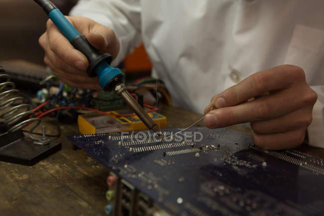 Primo piano dell'ingegnere robotico che monta il circuito stampato alla scrivania — Foto stock