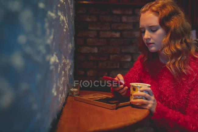 Rothaarige Frau benutzt Handy im Café — Stockfoto
