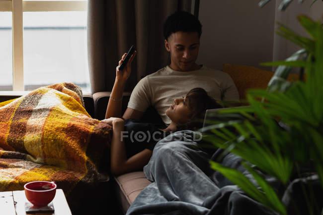 Casal usando telefone celular no sofá na sala de estar em casa — Fotografia de Stock