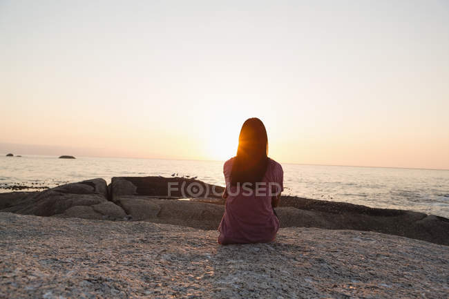 Rear view of woman sitting on beach — Stock Photo