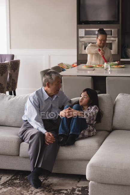 Grandfather and granddaughter interacting with each other on sofa in living room at home — Stock Photo