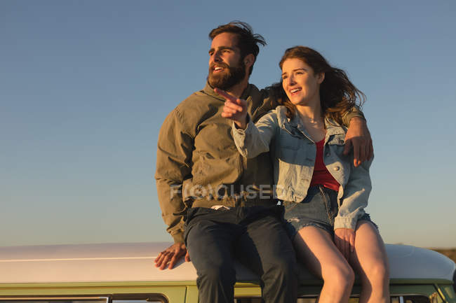 Couple sitting top of the van on road trip — Stock Photo