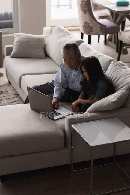 Grandfather and granddaughter using laptop on sofa in living room at home — Stock Photo