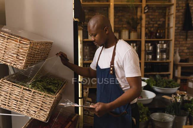 Внимательный персонал мужского пола проверяет акции в супермаркете — стоковое фото