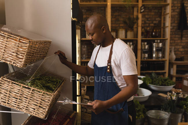 Attentive male staff checking stock in supermarket — Stock Photo