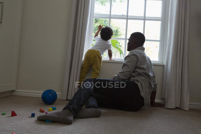 Father and son sitting near window at home — Stock Photo