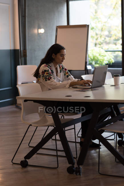Attentive businesswoman using laptop in office — Stock Photo