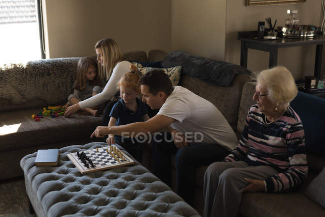 Multi generation family playing games on sofa in living room at home — Stock Photo