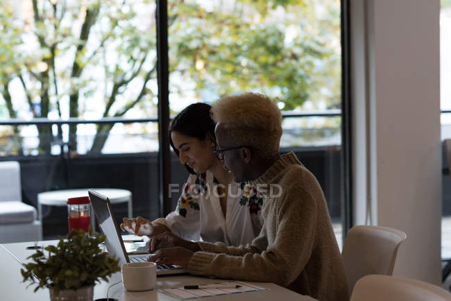 Business executives using laptop and digital tablet in office — Stock Photo