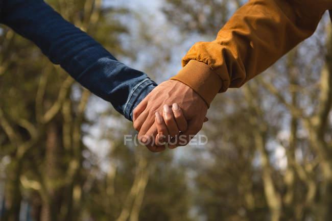 Primer plano de tenencia de pareja de las manos en la ciudad de - foto de stock