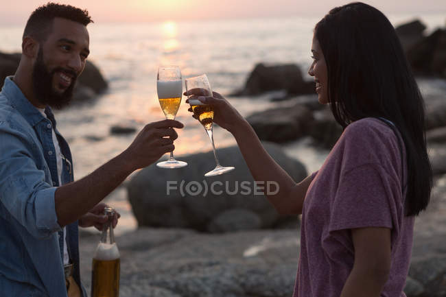 Happy couple toasting champagne glass near sea side — Stock Photo