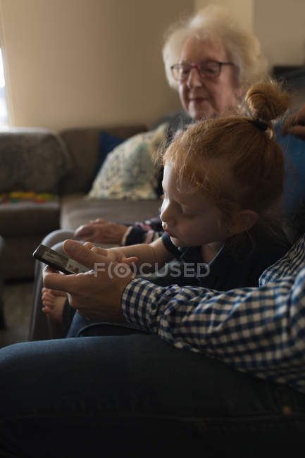 Multi generation family using mobile phone on sofa in living room at home — Stock Photo