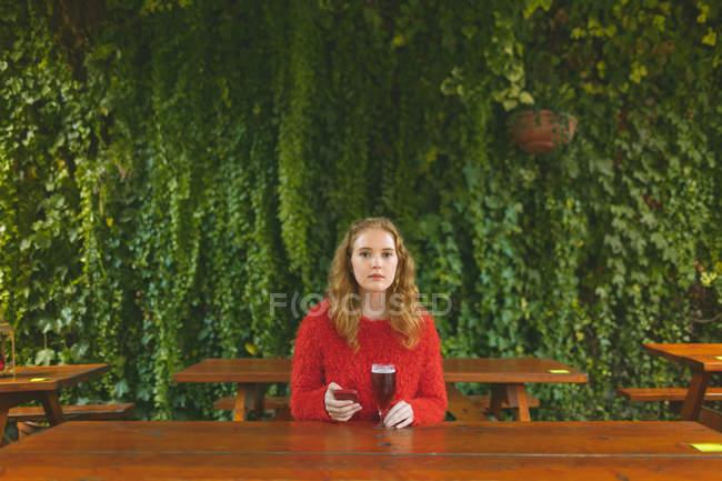 Рыжая женщина, с помощью мобильного телефона имея пива в кафе на открытом воздухе — стоковое фото