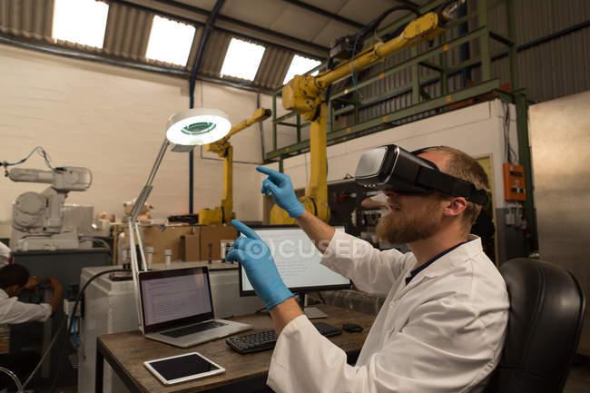 Робототехника инженер с помощью виртуальной реальности гарнитуры на стол на складе — стоковое фото