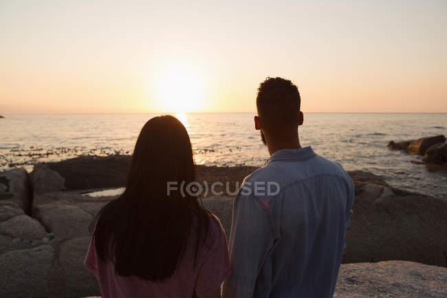 Rückansicht eines Paares, das an einem sonnigen Tag in der Nähe des Meeres steht — Stockfoto