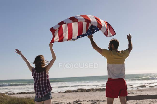 Vue arrière du couple tenant le drapeau américain sur la plage — Photo de stock
