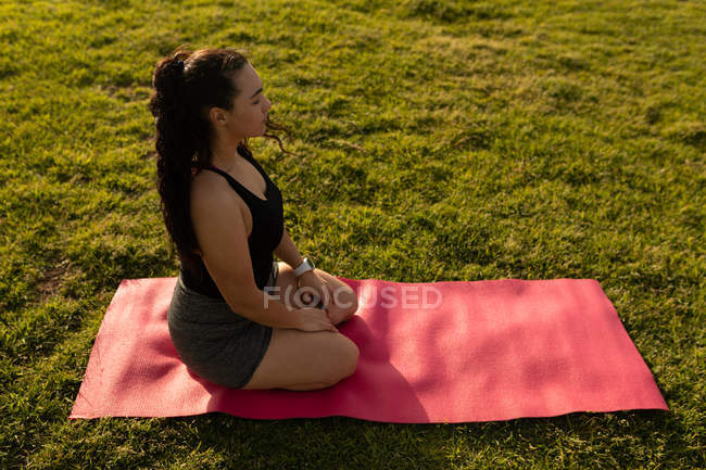 Side view of female jogger doing yoga in the park — Stock Photo
