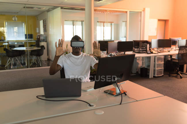 Business executive using virtual reality headset at desk in office — Stock Photo
