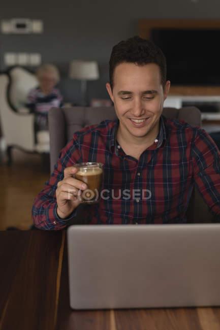 Hombre tomando café mientras usa el ordenador portátil en la sala de estar en casa - foto de stock