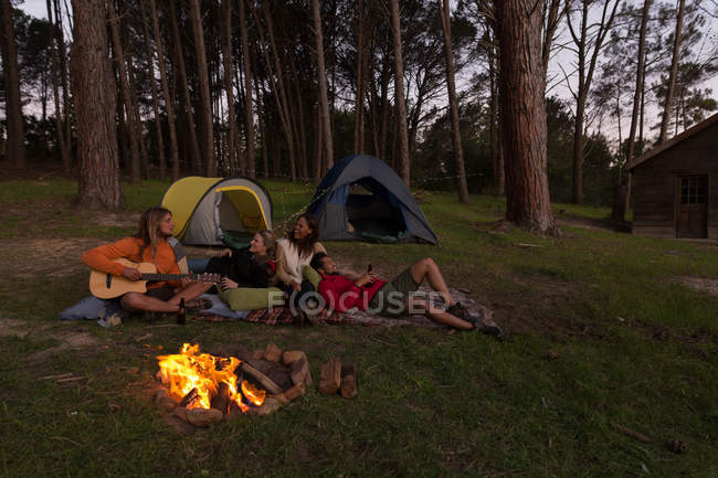 Group of friends having fun near campfire at campsite — Stock Photo