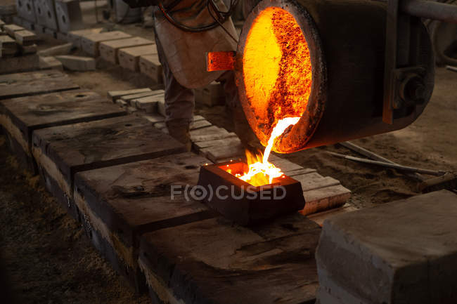 Worker pouring molten metal from flasks into moulds in foundry — Stock Photo