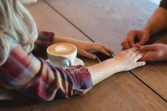 Coppia romantica che si tiene per mano nel caffè — Foto stock