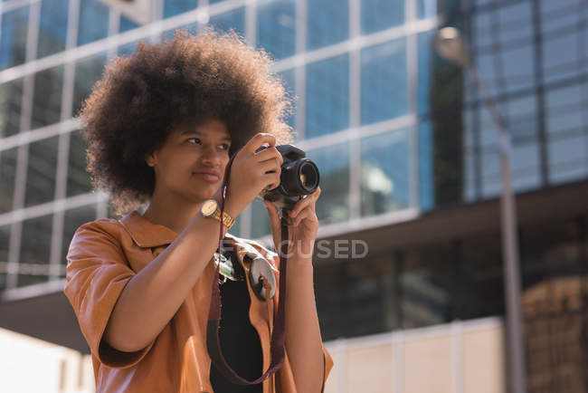 Woman clicking photo with digital camera in city — стоковое фото
