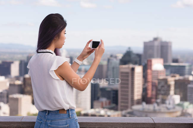 Side view of woman clicking photo on mobile phone — Stock Photo
