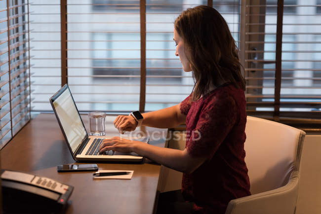 Businesswoman checking time on smartwatch while using laptop in hotel room — Stock Photo