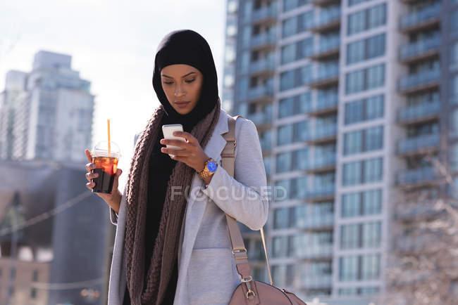 Хиджаб женщин, имеющих холодный кофе во время использования мобильного телефона — стоковое фото