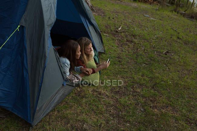 Junges Paar mit Handy im Zelt am Campingplatz — Stockfoto
