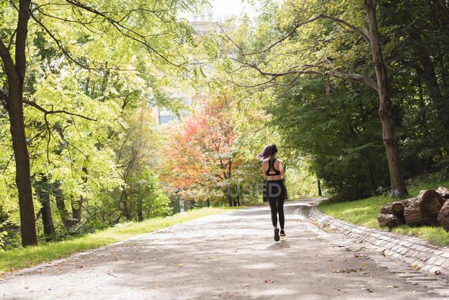 Vista posteriore del corridore femminile che corre nel parco — Foto stock