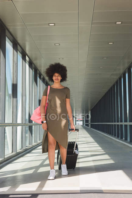 Stylish woman with luggage bag walking at airport — Stock Photo