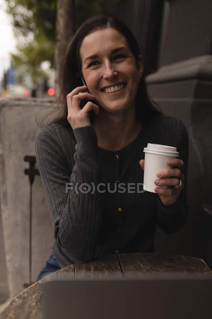 Счастливая женщина, говоря на мобильном телефоне в открытом кафе — стоковое фото