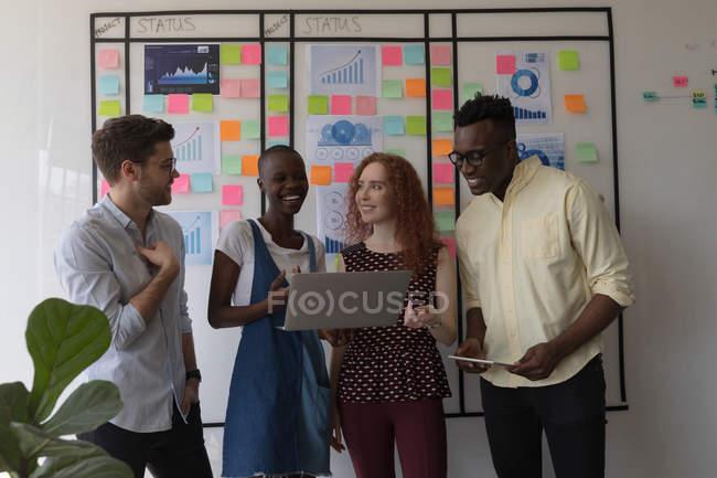 Счастливые руководители обсуждают за ноутбуком в офисе — стоковое фото