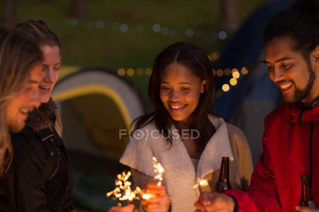 Group of friends having fun with sparklers at campsite — Stock Photo