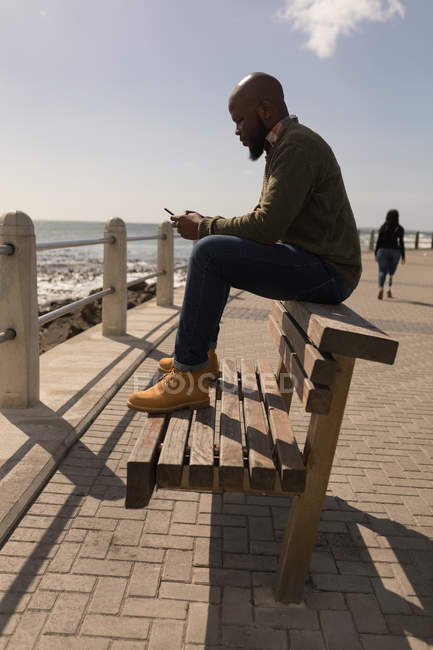 Side view of man using mobile phone on promenade — стоковое фото